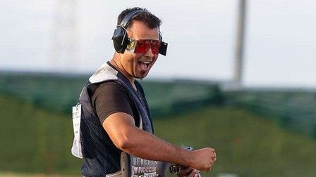 Olympic Trap Shooter Aaron Heading holding his gun and punching the air, smiling
