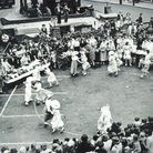 People dance in a circle, watched by a large crowd of people.