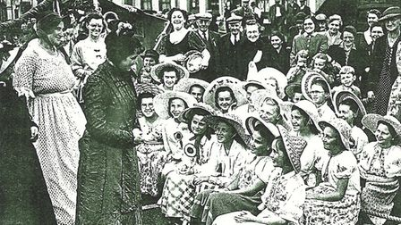 Two women dressed like Victorians talk to some girls wearing hats.
