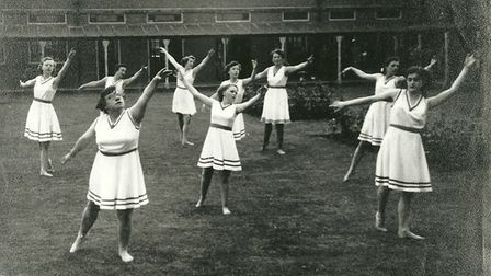 A group of young women wearing 1950s sports wear exercise.