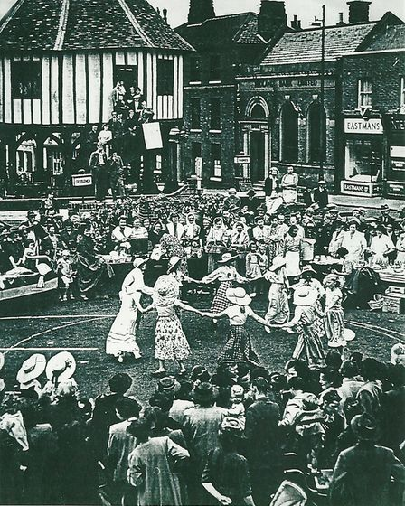 Women dance in a circle, watched by a large crowd of people.