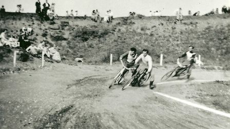 Men on bikes race around the speedway track. Fans sit and watch from the banks.