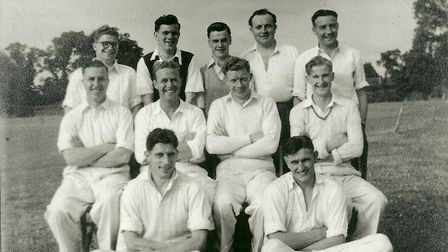 Men in cricket whites pose for a picture