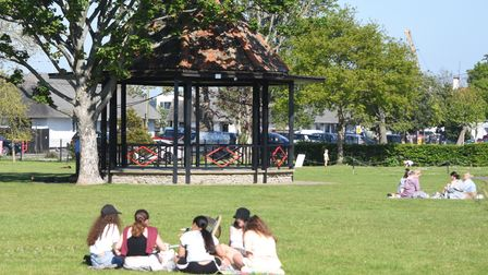 People enjoying the warm weather near the bandstand in Nicholas Everitt Park, Oulton Broad.