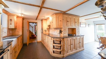 White-walled kitchen with pine units, Belfast sink, flagstone flooring, beamed ceiling and doors to back and right