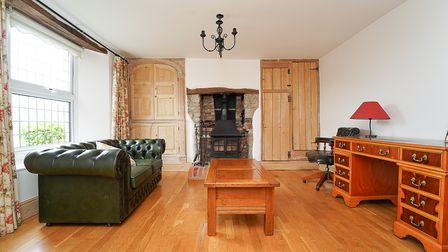 room with wooden floor, window on the left, leather coach in front, two doors either side of a fireplace with wood burner