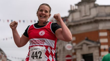 A runner crosses the finish line in Hitchin town centre after completing the Hitchin 10k on Sunday