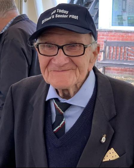 A man wearing a smart suit, a cap and glasses.