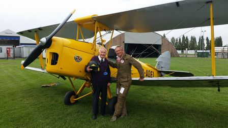 Two smartly dressed men stand in front of a yellow biplane