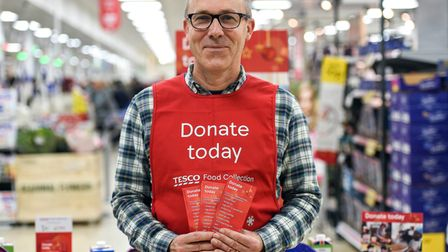 A Tesco volunteer holding a shopping list guide for donations at the launch of the Tesco Food Collection.