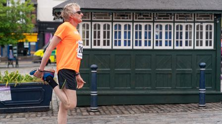 A runner stretches in Hitchin's Market Place - where the Hitchin 10k starts and finishes