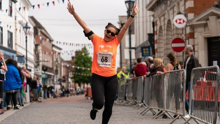A runner celebrates crossing the finish line at the Hitchin 10k on Sunday