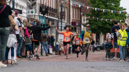 A runner reaches for a high five as she races towards the finish line of the Hitchin 10k on Sunday
