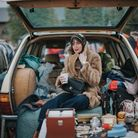 Vintage woman sits in classic car boot.