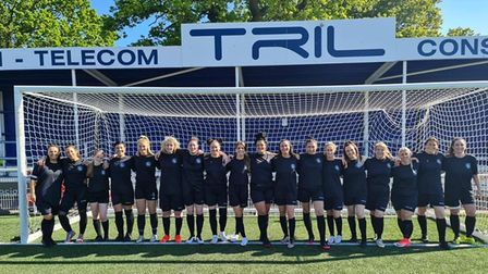 A women's football team. The women stand in front of a football goal wearing dark blue kit.
