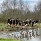 boys jumping into a dirty lake at an obstacle course in Romford.
