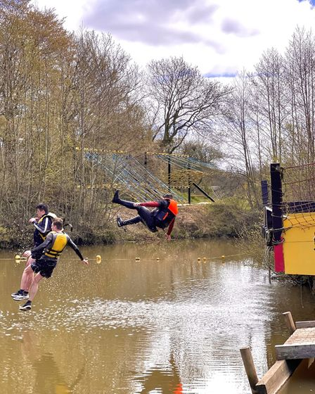 teenage boys throw themselves into a muddy lake at an assault course