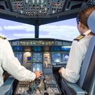 A male pilot and a female pilot flying an aeroplane, shot from behind with control panel visible