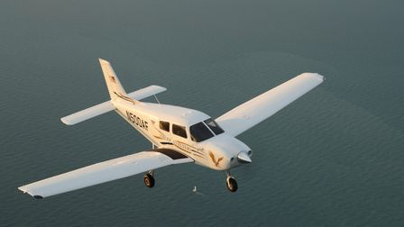 A Piper 100i aircraft flying above the sea