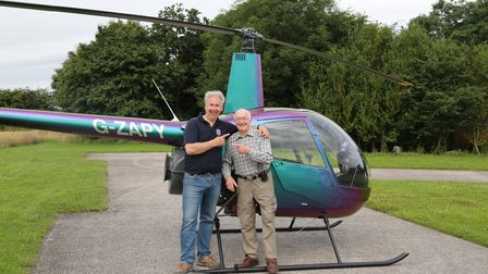 Two men stand in front of a green and purple helicopter