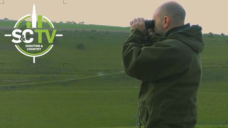 Man looking out over fields with binoculars