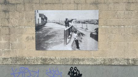 Monochrome photograph of a man with a telescope installed outside the Pleasure Beach.