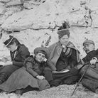 A group of holiday-makers sunning themselves on a south coast beach in 1895. Three of them have their noses in books