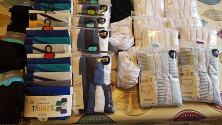 Lots of pants, socks and shirts on a table