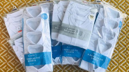Lots of packets of children's school shirts