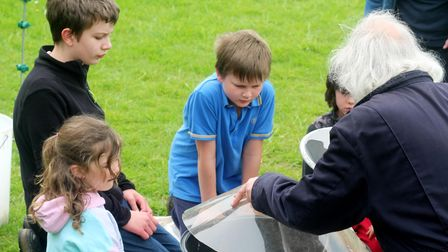 A group of children, and a supervisor, gather around a round contraption with a light on top: a moth trap