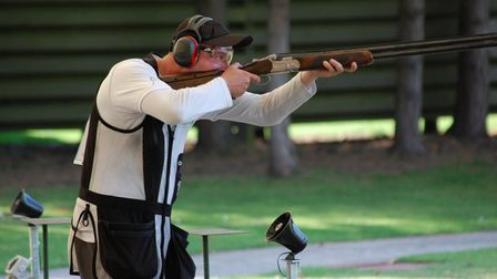 A man shooting the clay shooting discpline olympic trap with a shotgun
