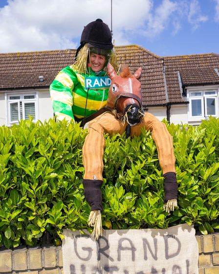 a scarecrow version of a grand national jockey jumping over a hedge