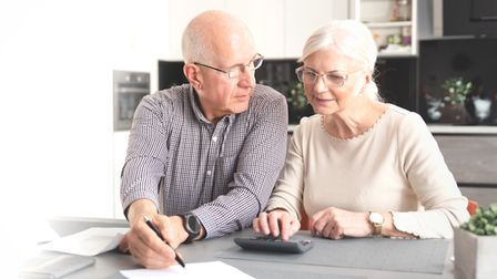 Senior couple calculating budget together. Retirees pay the bills. Web banner image background with