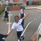 Three pupils in a playground. They are smiling, holding hands and running about