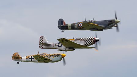 Spitfire MH434, Mustang TF51 Contrary Mary and aHispano Bouchon in flight over IWM Duxford.