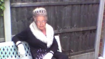 a woman sits on a bench with her dog beside her in a mask of the Queen.