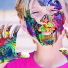 Boy covered in face paint and laughing