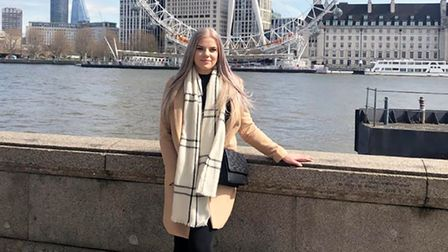 Holly Brooker in a coat and scarf stands in front of the London Eye smiling