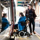 A woman in a wheelchair boards a train without any additional help