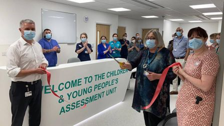 A team of nurses join together to watch the cutting of a ribbon to mark Queen's Hospital's new unit