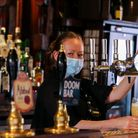 A bar worker pulls a pint for a customer; many pubs are facing a staff shortage