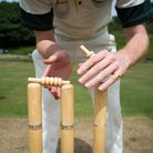 A player balancing bails onto the stumps