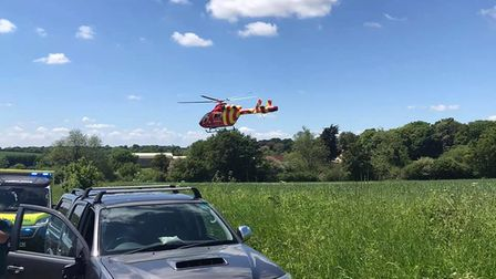 An air ambulance hovers over a lush green field.
