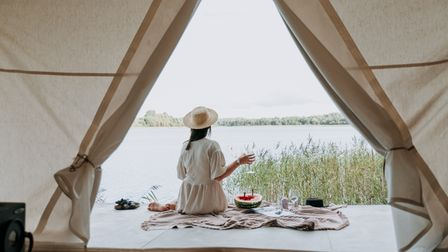 Through an open tent flap, we can see a woman with a picnic sat in front of a lake