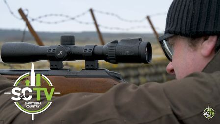 man looking down a rifle scope