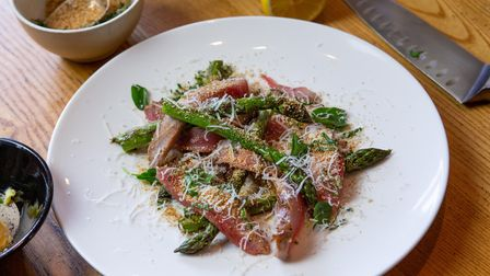a plate of smoked rabbit and asparagus on a wooden table
