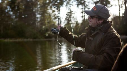a man fly fishing in a rowing boat