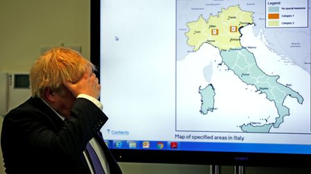 Britain's Prime Minister Boris Johnson gestures in front of a map of Italy during a visit to the Pub
