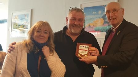 BishopJohn Mills presents a plaque to Cromer's Breakers cafe owners Nikki andMartin Rodwell