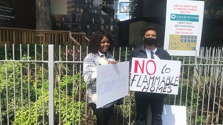 """Protesters hold up signs saying: """"No to flammable homes."""